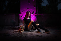 Girl in an abandoned building. With a Teddy bear in his hands royalty free stock images