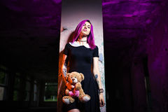 Girl in an abandoned building. With a Teddy bear in his hands stock photography