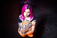 Girl in an abandoned building. With a Teddy bear in his hands stock image