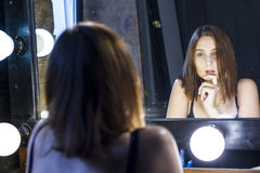 Sexy girl admires itself in mirror Stock Photography