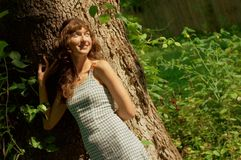 Girl Against Tree. Trunk in woods stock photography