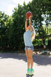 Sexy girl on the basketball court. Posing and playing with a basketball ball Royalty Free Stock Images