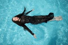 Sexy girl bathes in pool. Beautiful woman in black dress floating in blue water Royalty Free Stock Photo