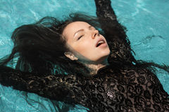 Sexy girl bathes in pool. Portrait of the beautiful woman in black dress floating in blue water Royalty Free Stock Images