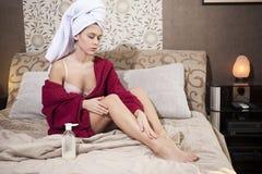 Sexy girl in bathrobe applying cream Stock Photography