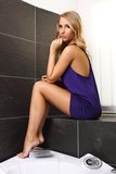 Sexy girl in the bathroom. Beautiful blond woman in nightgown sitting on the parapet in the bathroom, interior photography, glamour and boudoir photo Royalty Free Stock Images