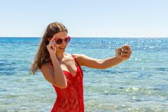 Girl on a beach with surprised expression looking at phone and taking selfie.  royalty free stock photos