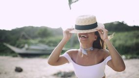 girl with a beautiful smile in a hat laughing on the beach