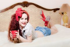 Sexy girl in bed holding red cup of hot drink Stock Photography