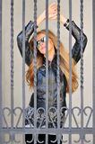 Girl behind bars. Girl posing behind bars stock image