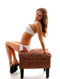 Girl in bikini. Girl sitting on a bench in a white bikini royalty free stock photography