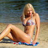 Sexy girl in bikini on the beach. Smiling sexy girl in bikini sunbathing at the beach on a background of water Stock Images