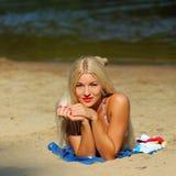Sexy girl in bikini on the beach. Smiling sexy girl in bikini sunbathing at the beach on a background of water Stock Image