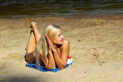 Sexy girl in bikini on the beach. Smiling sexy girl in bikini sunbathing at the beach on a background of water Stock Photos