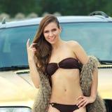 Sexy girl in bikini. Beautiful sexy girl in bikini and in fur cape posing on a background of golden car. sexy lady near the golden car Stock Photo