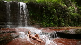 girl with bikini lying down in waterfall river
