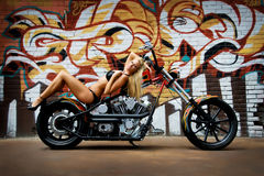 Sexy Girl Bikini on Motorcycle. Sexy Girl on Motorcycle with blond hair wearing 2 piece bikini laying on her back against graffiti wall background Royalty Free Stock Image