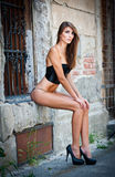 Sexy girl in bikini posing fashion near red brick wall on the street Stock Photography