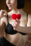 Sexy girl in black bra holds red heart for Valentine�s day Royalty Free Stock Photography