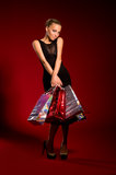 Sexy girl in a black dress with bags in hands Stock Images