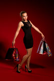 Sexy girl in a black dress with bags in hands Royalty Free Stock Photos