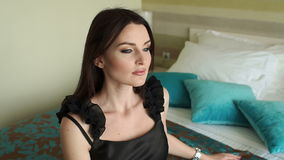 Sexy girl in black dress sitting on bed, close-up. Gorgeous sexy girl in a black dress is sitting on the bed, next to her are blue pillows. Slow motion stock video footage