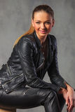 Sexy girl in black leather posing seated resting her hands Stock Photos