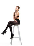 Sexy girl in black pantyhose  and bra sit on chair Royalty Free Stock Photos