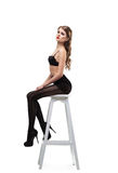 Sexy girl in black pantyhose  and bra sit on chair Stock Images