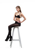 Sexy girl in black pantyhose  and bra sit on chair Royalty Free Stock Image