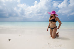 Sexy girl in black swimsuit, hat and sunglasses on his knees in Stock Images