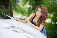 Sexy girl in black vest is posing on hood car. The Sexy girl in black vest is posing on hood car Stock Photos