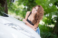 Sexy girl in black vest is posing on hood car. The Sexy girl in black vest is posing on hood car Royalty Free Stock Photos