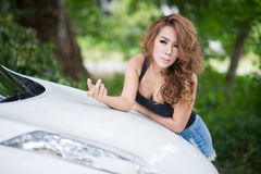 Sexy girl in black vest is posing on hood car. The Sexy girl in black vest is posing on hood car Royalty Free Stock Photography