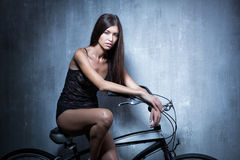 Sexy girl in a black vest and shorts sitting on the bike on the Stock Images