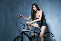 Sexy girl in a black vest and shorts sitting on the bike on the Stock Photos