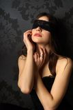 Sexy girl blindfolded. Young beautiful girl with a lace blindfold Stock Image
