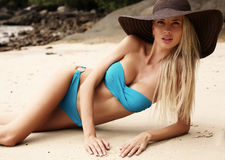 girl with blond hair in bikini and elegant hat relaxing on beach Royalty Free Stock Photo