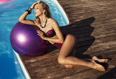 Sexy girl with blond hair in bikini beside a swimming pool Royalty Free Stock Photos