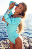 Sexy girl with blond hair in elegant blue swimsuit posing on beach. Fashion outdoor photo of sexy beautiful woman with long blond hair wearing elegant blue Royalty Free Stock Photography