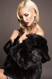 Sexy girl with blond hair in fur coat Royalty Free Stock Image