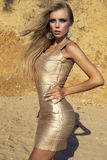Sexy girl with blond hair in gold dress posing on beach Royalty Free Stock Images