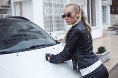 Sexy girl with blond hair in leather jacket posing beside a car Stock Images