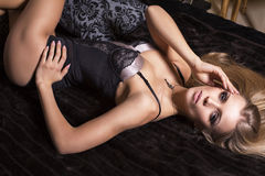 Sexy girl with blond hair in lingerie lying on the bed Stock Photo