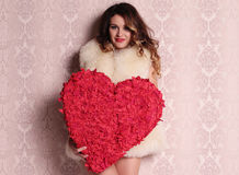 Sexy girl with blond hair posing with heart, symbol of Valentine's day Royalty Free Stock Photos