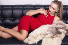 Sexy girl with blond hair in red dress with fur Stock Photos