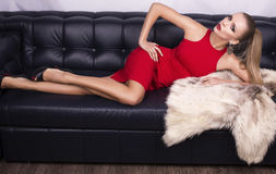 Sexy girl with blond hair in red dress with fur Stock Photography