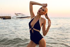 Sexy girl with blond hair in swimsuit posing on beach Stock Photo