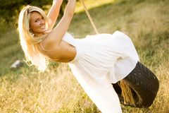Sexy Girl Blonde on Tire Rope Swing Royalty Free Stock Photography