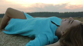 Sexy girl in blue dress lying in the hay. stock video footage